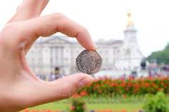 Dinero inglés del penique que representa a la reina delante de Buckingham P Foto de archivo