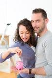 Dinero joven del ahorro de los pares en una hucha Imagen de archivo libre de regalías