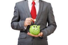 Dinero joven del ahorro del hombre de negocios Imágenes de archivo libres de regalías