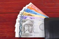 Dinero kirguizio en la cartera negra imagen de archivo