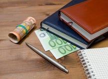 Dinero, libreta y pluma Fotos de archivo