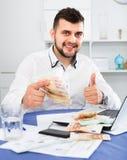 Dinero masculino joven de la ganancia del hombre de negocios fácilmente en línea en Internet foto de archivo libre de regalías