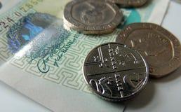 Dinero - monedas y un billete de banco, con el foco en la moneda de 5 peniques Fotografía de archivo