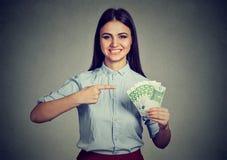 Dinero Mujer de negocios que mira la cámara que señala en el efectivo Fotos de archivo