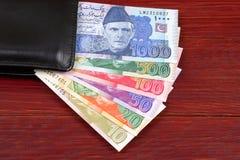 Dinero paquistaní en la cartera negra imágenes de archivo libres de regalías