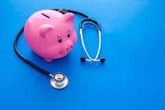 Dinero para el tratamiento Costos médicos Moneybox en la forma del cerdo cerca del estetoscopio en espacio azul de la copia del f fotografía de archivo libre de regalías