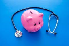 Dinero para el tratamiento Costos médicos Moneybox en la forma del cerdo cerca del estetoscopio en fondo azul fotos de archivo