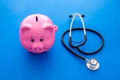 Dinero para el tratamiento Costos médicos Moneybox en la forma del cerdo cerca del estetoscopio en fondo azul fotografía de archivo libre de regalías