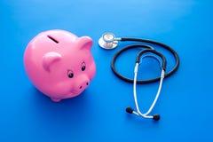 Dinero para el tratamiento Costos médicos Moneybox en la forma del cerdo cerca del estetoscopio en fondo azul foto de archivo