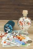 Dinero para el tratamiento costoso Dinero y píldoras Píldoras de diversos colores en el dinero Billetes de banco euro auténticos Fotos de archivo libres de regalías