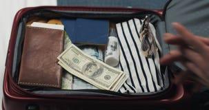 Dinero para el viaje Manos de la mujer que cuentan billetes de dólar en el fondo de la maleta La muchacha va en un viaje La malet almacen de metraje de vídeo