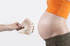Dinero para la panza embarazada Fotos de archivo libres de regalías