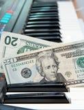 Dinero pegado en teclado del órgano eléctrico Imágenes de archivo libres de regalías