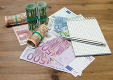 Dinero, pluma y cuaderno euro Foto de archivo libre de regalías