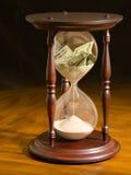 Dinero que desaparece en los errores financieros de cristal de la hora Fotos de archivo libres de regalías