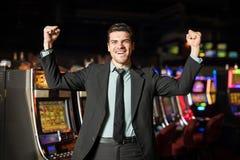 Dinero que gana del hombre en un casino foto de archivo