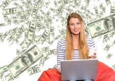 dinero que manda un SMS Mujer joven con el ordenador portátil, dinero por todas partes Fotografía de archivo libre de regalías