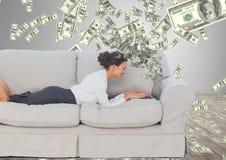 dinero que manda un SMS Mujer joven feliz en el sofá con el ordenador portátil Dinero que sube del ordenador portátil imágenes de archivo libres de regalías