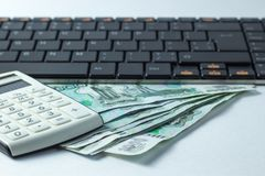 Dinero que miente en el teclado, un concepto para comprar el nuevo ordenador Fotografía de archivo