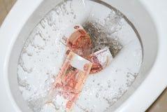 Dinero rasante en el retrete fotografía de archivo libre de regalías