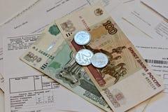 Dinero ruso - billetes y monedas - en recibos de facturas de servicios públicos Foto de archivo