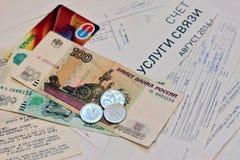 Dinero ruso - billetes y monedas, y pago plástico de la tarjeta en recibos de facturas de servicios públicos Imagen de archivo libre de regalías