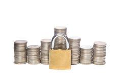 Dinero seguro Monedas y candados aislados en un fondo blanco Imagenes de archivo