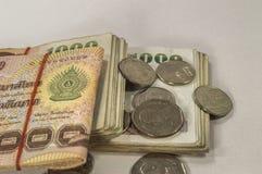 Dinero tailandés, 1000 billetes de banco del baht y moneda en el fondo blanco Imágenes de archivo libres de regalías