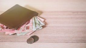 Dinero tailandés en la cartera de Brown y moneda de plata en el escritorio de madera fotos de archivo