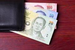 Dinero tailandés en la cartera negra foto de archivo