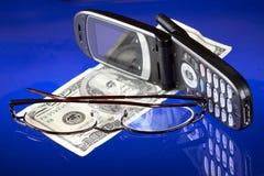 Dinero, teléfono sin hilos y lentes Fotos de archivo