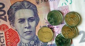 Dinero ucraniano Billete de banco del hryvnia ucraniano Fondo de doscientos billetes de banco del hryvnia, monedas en las pilas,  fotografía de archivo libre de regalías