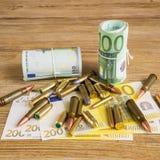 Dinero y balas Foto de archivo libre de regalías