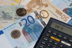 Dinero y calculadora y anillo en el año 2015 Imágenes de archivo libres de regalías