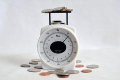 Dinero y cambio en una escala del peso Foto de archivo libre de regalías