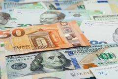 Dinero y concepto de las finanzas Cientos nuevas cuentas del d?lar en fondo abstracto colorido del nacional ucraniano, americano  fotografía de archivo libre de regalías
