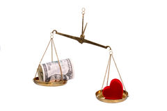 Dinero y corazón en escalas. Imagenes de archivo