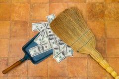 Dinero y escoba Imagenes de archivo