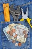 Dinero y herramienta en bolsillo de los vaqueros Foto de archivo libre de regalías