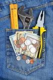Dinero y herramienta en bolsillo de los vaqueros Fotos de archivo