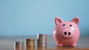 Dinero y hucha crecientes del paso de la pila de la pila del dinero Ahorros del concepto con la hucha y las monedas apiladas Aisl almacen de video