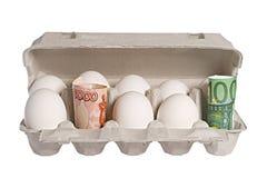 Dinero y huevos Imagen de archivo libre de regalías