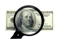 Dinero y lupa Imágenes de archivo libres de regalías