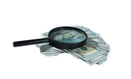 Dinero y lupa Imagen de archivo libre de regalías