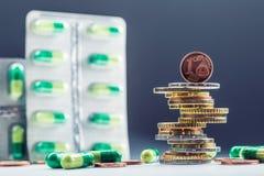 Dinero y medicamentos euro Monedas y píldoras euro Monedas apiladas en uno a en diversas posiciones y libremente píldoras alreded Fotografía de archivo
