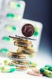 Dinero y medicamentos euro Monedas y píldoras euro Monedas apiladas en uno a en diversas posiciones y libremente píldoras alreded Foto de archivo libre de regalías