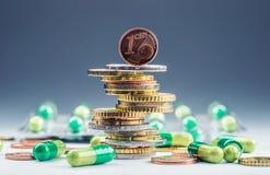 Dinero y medicamentos euro Monedas y píldoras euro Monedas apiladas en uno a en diversas posiciones y libremente píldoras alreded Imagen de archivo