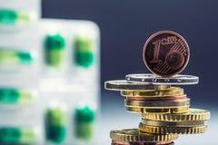 Dinero y medicamentos euro Monedas y píldoras euro Monedas apiladas en uno a en diversas posiciones y libremente píldoras alreded Fotos de archivo libres de regalías