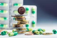 Dinero y medicamentos euro Monedas y píldoras euro Monedas apiladas en uno a en diversas posiciones y libremente píldoras alreded Fotografía de archivo libre de regalías