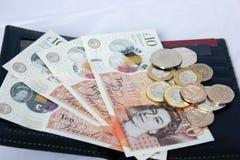 Dinero y monedas ingleses en la cartera de cuero Foto de archivo